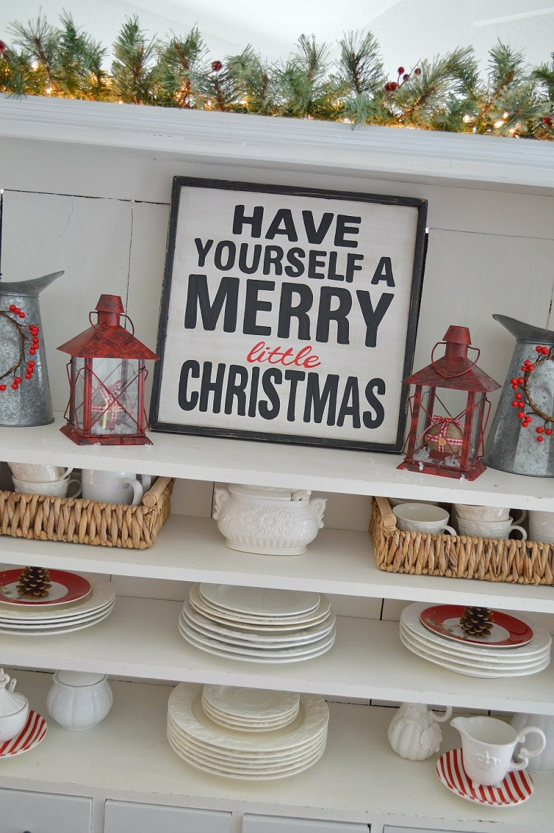 Apothecary Cabinet Open Cabinet Shelves with our Have Yourself A Merry Little Christmas wood sign. Red Lanterns filled with Plaid and Gingham Check ornaments. It's a Cottage Christmas Home Tour at foxhollowcottage.com