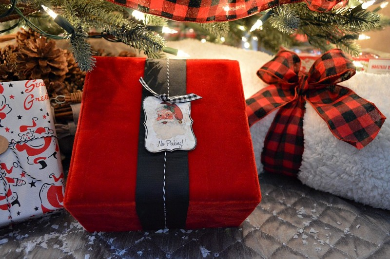 Red velvet Christmas present with black ribbon and vintage Santa Claus gift tag