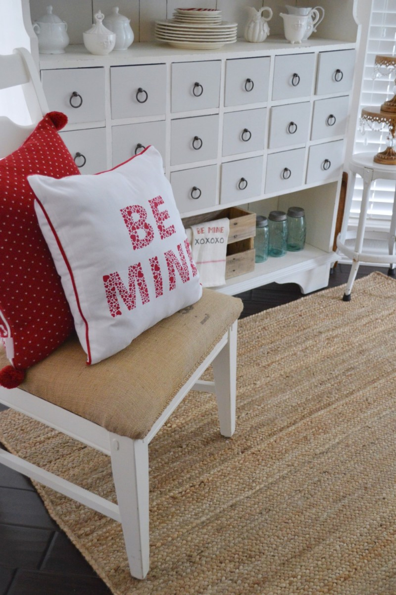 9 The apothecary cabinet decorated for Valentine's Day - foxhollowcottage.com - Be Mine pillow, sisal braided rug, diy coffee sack chair makeover project