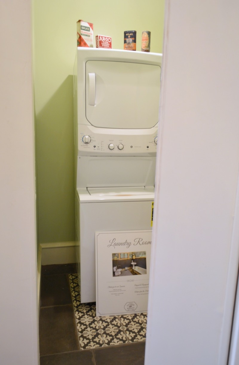 Hidden laundry room, stackable washer and dryer behind a bookcase - Secret room in old vintage home.