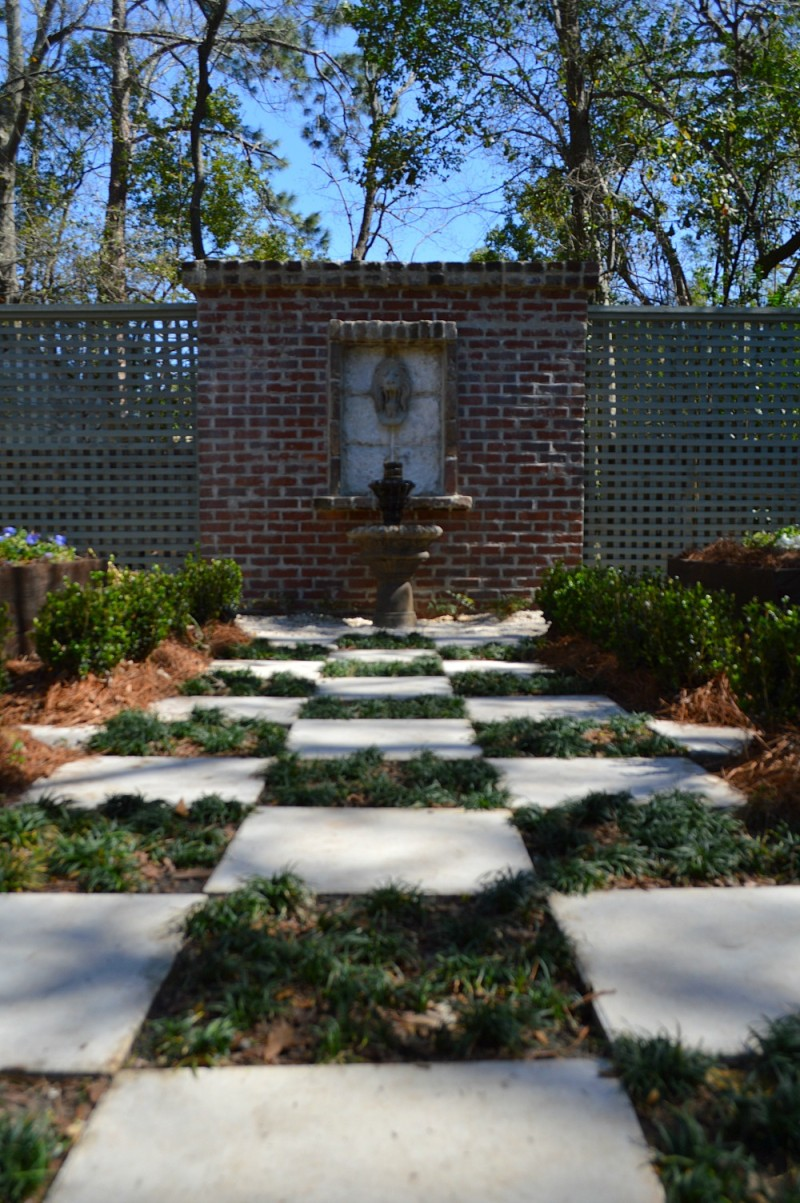 Fountains and lions head yard art decor with vintage used brick, original to the home - Southern fixer upper back yard.
