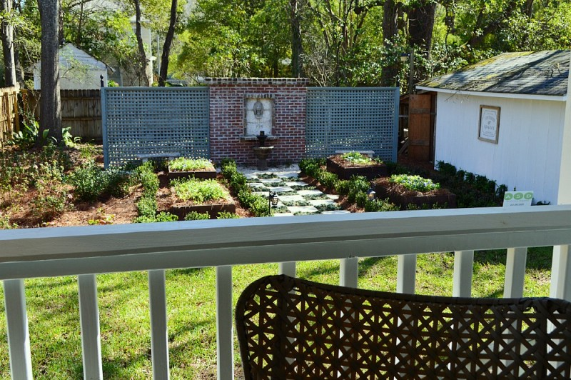 Landscaped Backyard with aqua lattice, brick and lions head accent wall - pavers and step-able plants walkway, raised flower beads. A Southern fixer up home renovation.