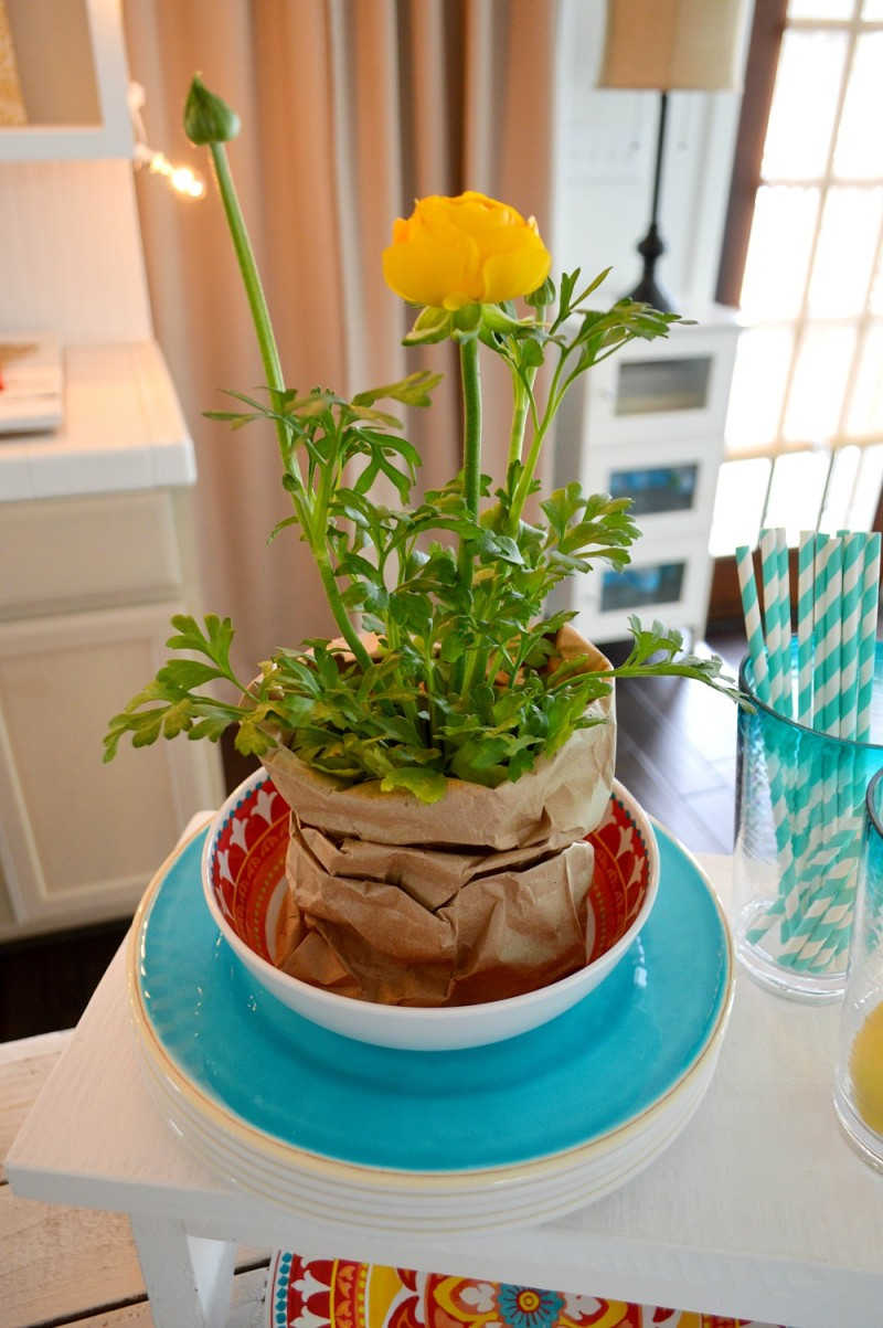 Pop potted flowers around the table to bring the outdoor feel inside. Use paper sacks as a quick substitute if you don't have time to pot them. Shown: Yellow Ranunculus