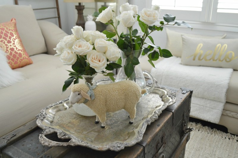 Spring at the cottage - foxhollowcottage.com - Living room; vintage steamer trunk coffee table, Hello + coral pillows, white roses, old door mirror