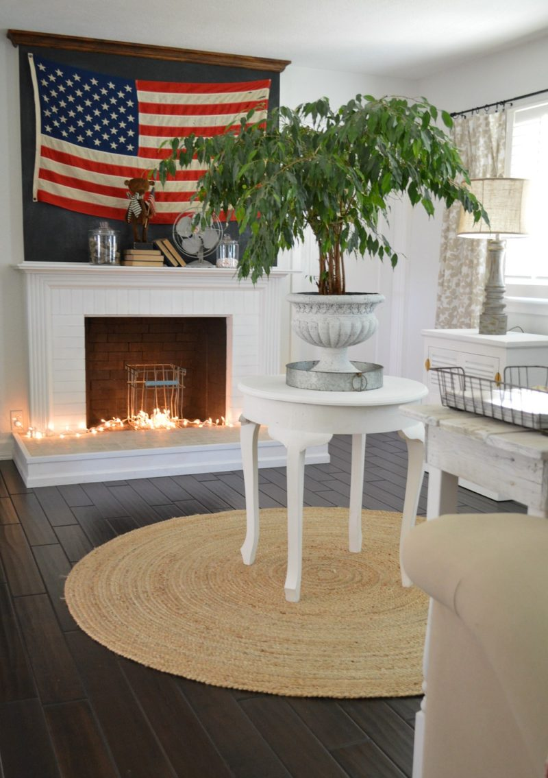 Coastal cottage entryway with a nautical feel. US flag mantel display, potted Ficus, dark wood floors.