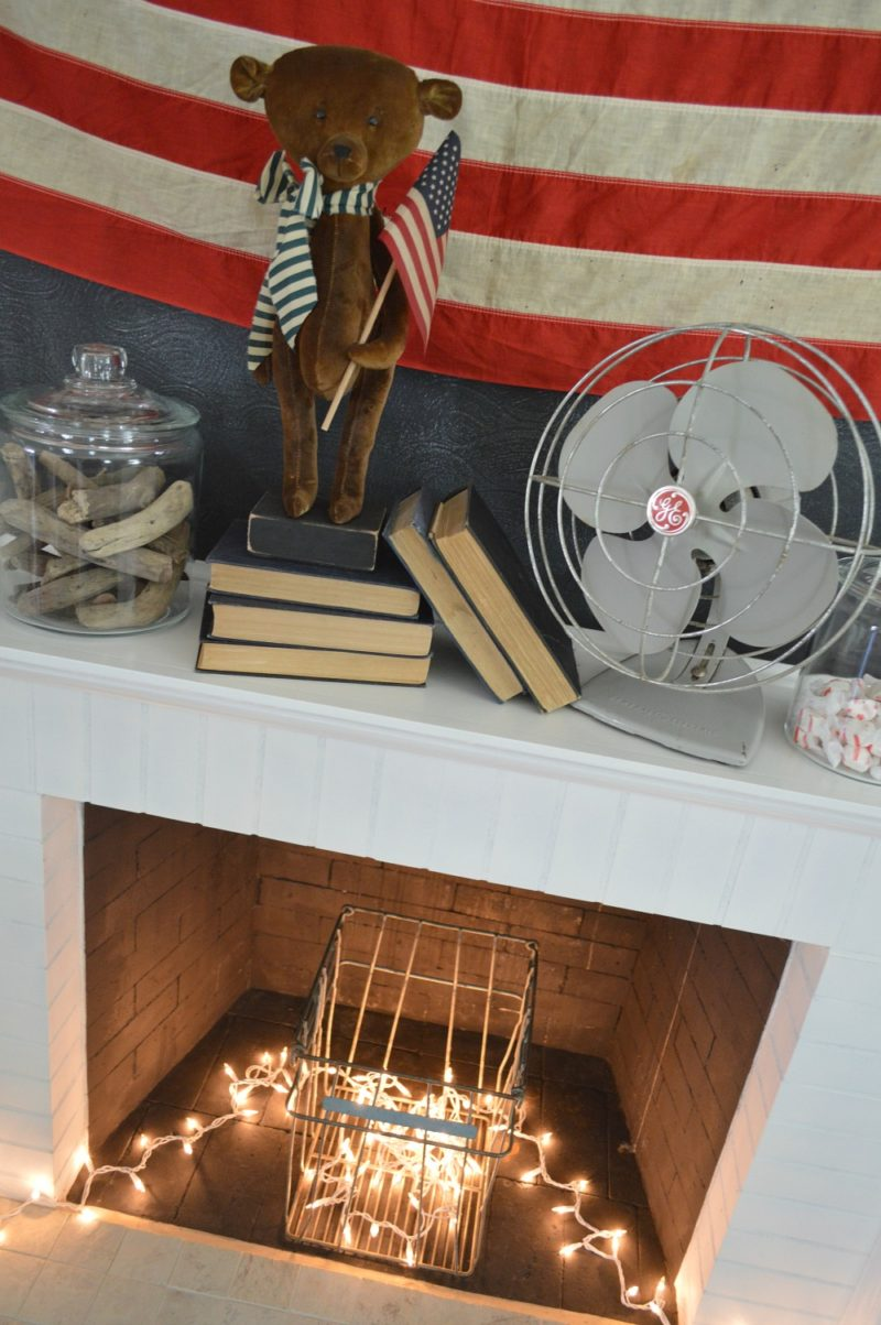 Patriotic fireplace mantel with vintage eggg crate, lights and teddy bear with flag