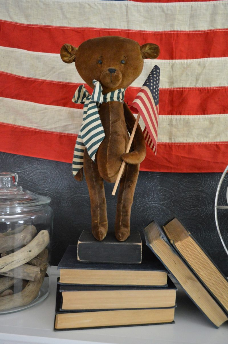 Vintage teddy bear with flag, patriotic fireplace mantel.