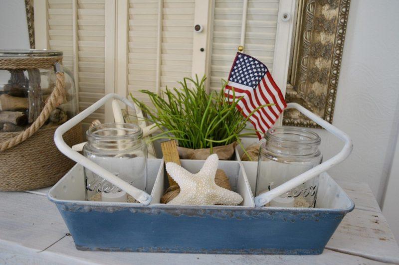 HomeGoods blue tin basket, vintage ball jars, sand, candles, US flag, seashells and twine.