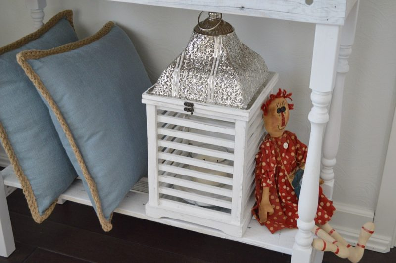 Summer cottage on the coast. Shuttered lantern, white wood console table, raggedy ann doll