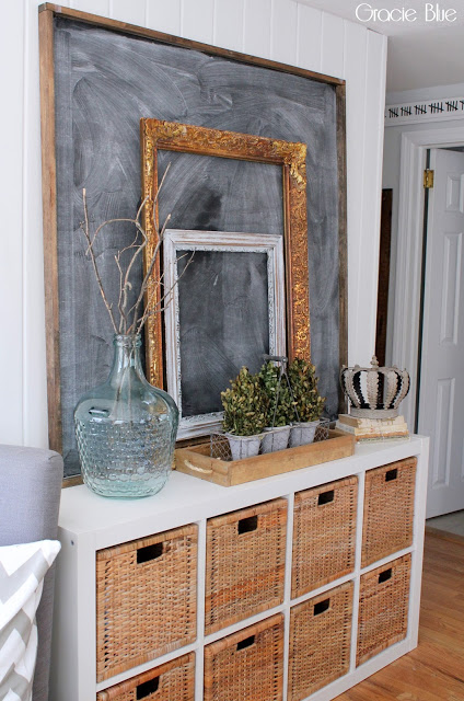 Entryway console with basket cubby shelves. Barn shiplap with chalkboard and layered frames.