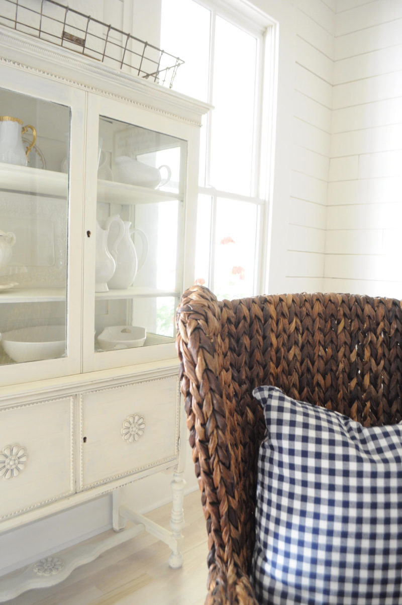 White Farmhouse Dining Room - Buffalo Check Accents in the Throw Pillow and Natural Woven Captains Chair add Color & Texture