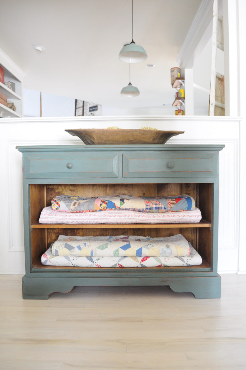 Old chippy aqua chest holds a vintage quilt collection and a dough bowl. Love the light fixtures peeking over from the kitchen too! Life On The Shady Grove Farmhouse Home Tour
