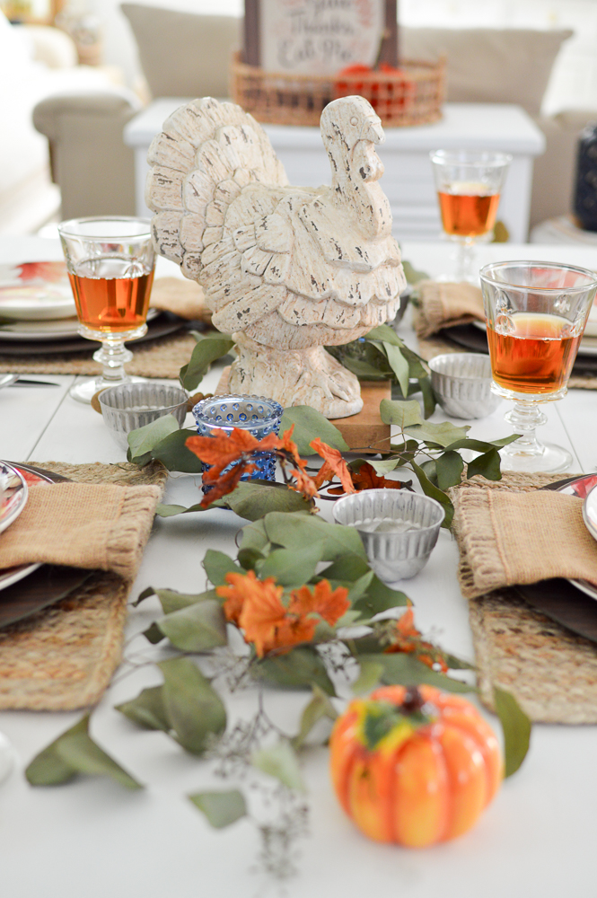 Beginner Friendly Thanksgiving Tablescape with Turkey centerpiece, leaves and candles.