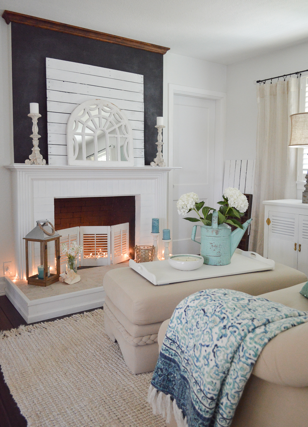 Casual Coastal Cottage Home - www.foxhollowcottage.com - Chalk painted fireplace, vintage watering can, twinkle lights
