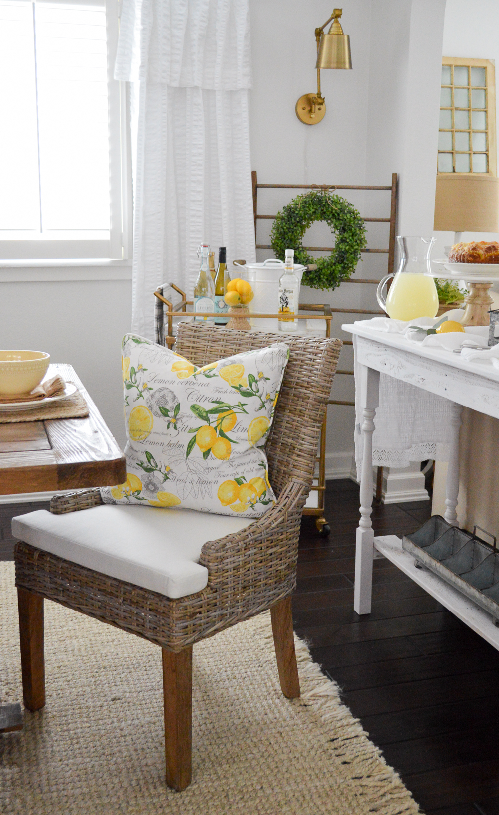 farm table dining in a cottage home - lemon pillow, woven chair, brass wall sconce, bar cart.