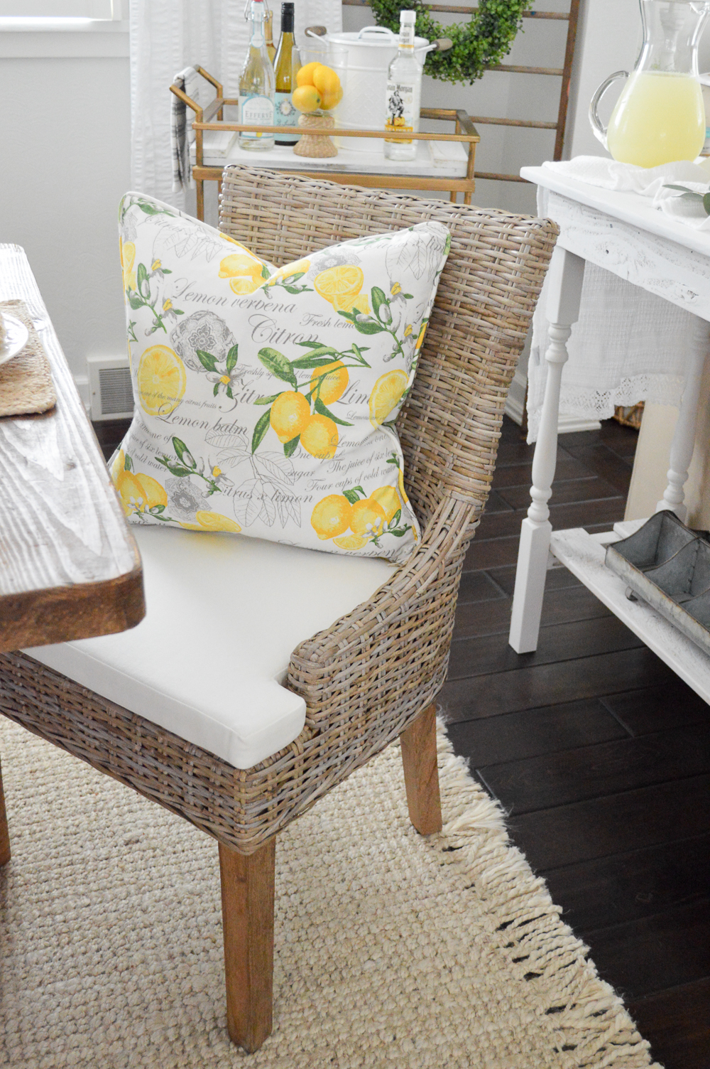 Woven wicker dining chair with washable seat cushion. Love the lemon pillow!