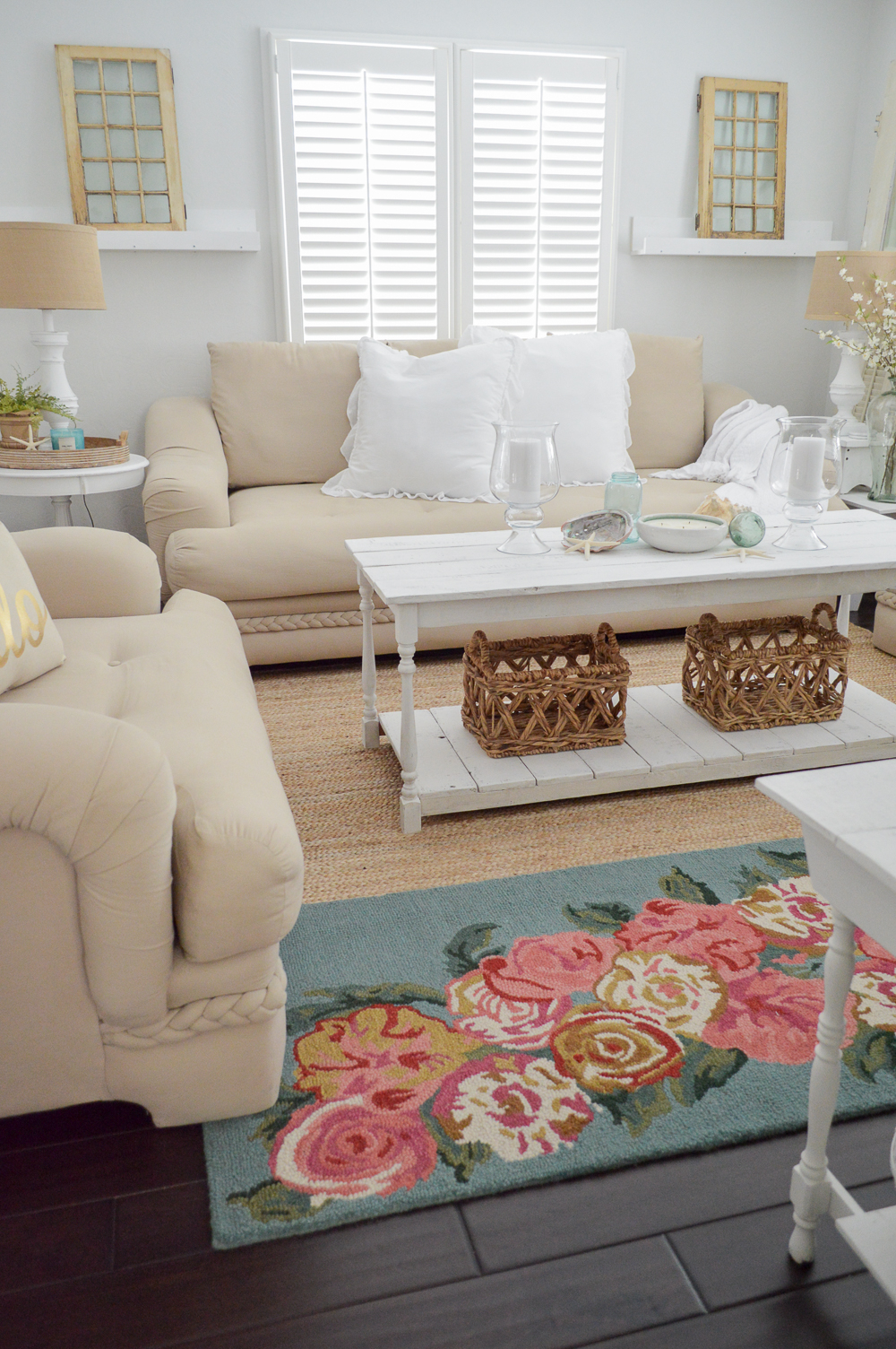 Soft, sandy neutral sofa and chair, with white furniture and wood floors. The floral layered rug adds color and interest to the space!
