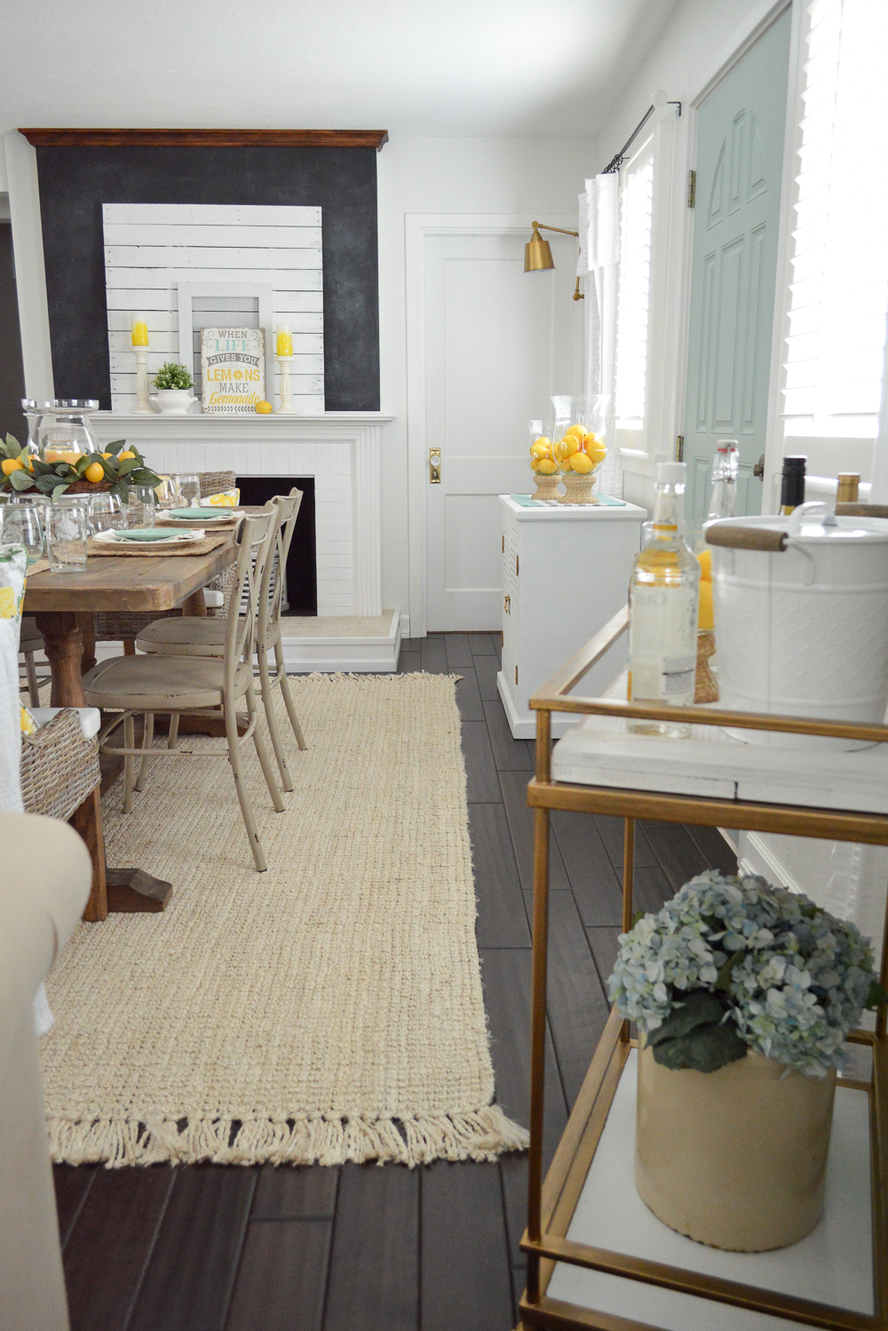 Simple Summer Decorating Ideas and Home Tour - woven sisal rug, wood floors, diy fieplace, car cart, brass wall sconce lights