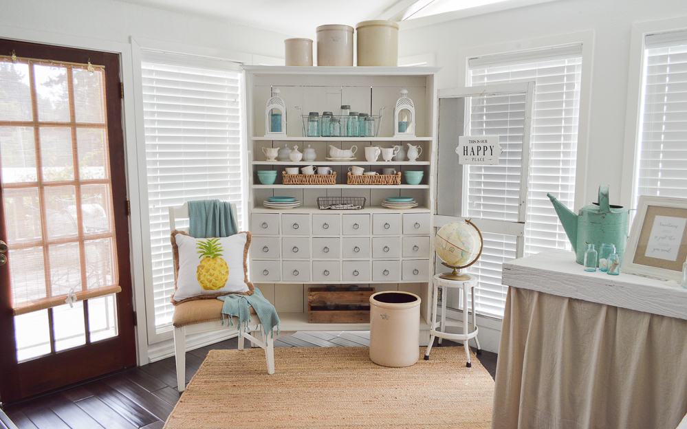 Simple Summer Decorating Ideas and Home Tour - sun room, apothecary cabinet, aqua, pineapple pillow, vintage crock collection.